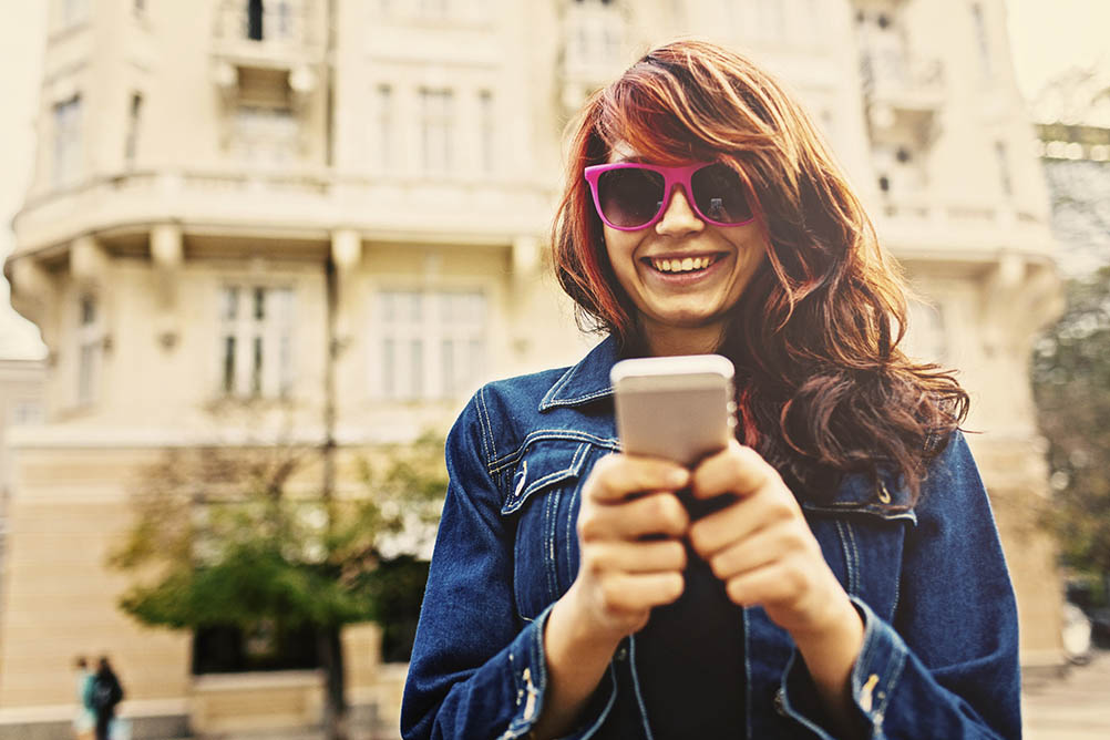 Smiling young woman holds her phone in front of her