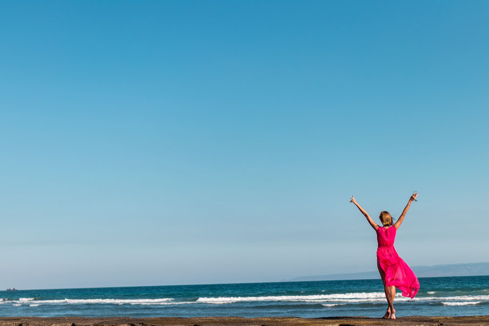 A woman celebrates a lottery win next to the sea against a blue-sky background