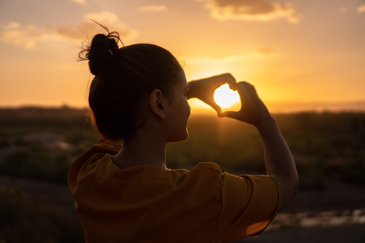 Woman watching sunset making heart shape with her fingers.