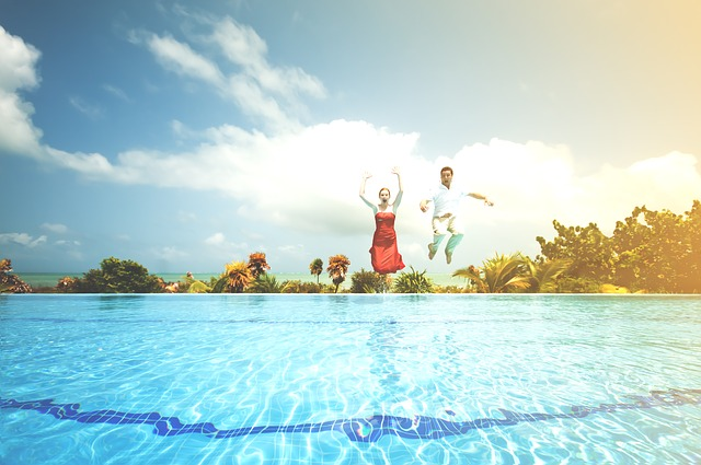 Happy couple jump into a swimming pool to celebrate their lottery win