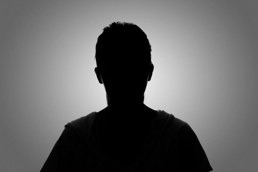 Silhouette of anonymous lottery winner against a grey background